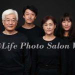 黒シャツ、黒背景でポスターのような家族写真撮影
